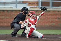 Dayton Flyers catcher Chase Melnick (4) reaches for a high pitch as home plate umpire Cody Clark looks on during the game against the Campbell Camels at Jim Perry Stadium on February 28, 2021 in Buies Creek, North Carolina. The Camels defeated the Flyers 11-2. (Brian Westerholt/Four Seam Images)