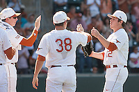 Texas Longhorns starting pitcher Dillon Peters #32 is greeted by his teammates after being lifted in the eighth inning of the NCAA baseball game against the Oklahoma Sooners on April 6, 2013 at UFCU DischFalk Field in Austin, Texas. The Longhorns defeated the rival Sooners 1-0. (Andrew Woolley/Four Seam Images).