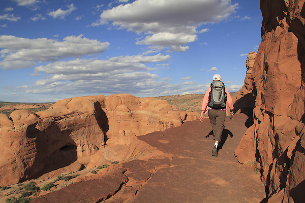 Woman on hiking trail leading to Delicate Arch in Arches National Park, Moab, Utah, USA. .  John leads hiking and photo tours throughout Colorado. .  John offers private photo tours in Arches National Park and throughout Utah and Colorado. Year-round.