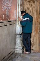 Jaipur, Rajasthan, India.  Young Man Praying at the Govind Devji Hindu Temple.