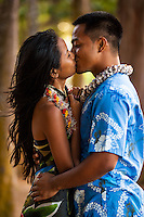 A young, engaged local couple kiss at Kailua Beach Park, Windward O'ahu.