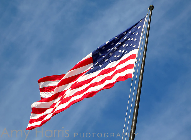 American flag waving in the wind with blue sky background.
