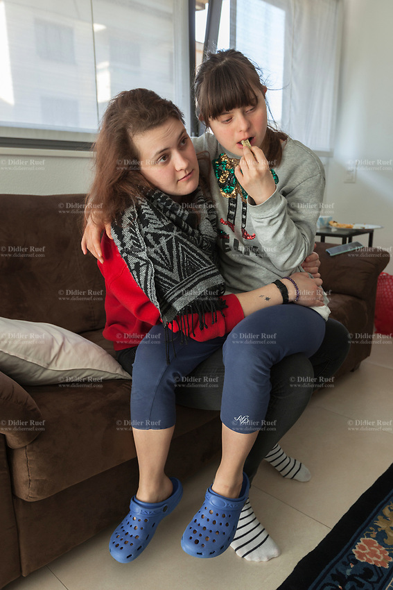 Switzerland. Canton Ticino. Mendrisio. Living room. (Left to right) Micol Mereu (20) hugs her young sister Gaia (18) in her arms while seated on the couch. Gaia Mereu is a dancing member of MOPS_DanceSyndrome which is an independent Swiss artistic, cultural and social organisation operating in the field of contemporary dance and disability. It is composed only of Down dancers. Down syndrome (DS or DNS), also known as trisomy 21, is a genetic disorder caused by the presence of all or part of a third copy of chromosome 21 It is usually associated with physical growth delays, mild to moderate intellectual disability, and characteristic facial features. 7.03.2020 © 2020 Didier Ruef