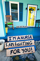 """Signs sit on a front porch in the Stanton Heights neighborhood that read """"Flatten the curve"""" and """"I'm a nurse. I am fighting for you! We will be OK!"""" on Friday April 3, 2020 in Pittsburgh, Pennsylvania. (Photo by Jared Wickerham/Pittsburgh City Paper)"""