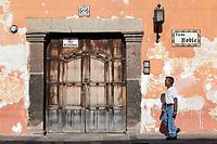 Antigua, Guatemala.  Doorway, Sidewalk, Person Walking.