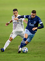 CARSON, CA - OCTOBER 18: Jake Nerwinski #28 moves with the ball past Cristian Pavon #10 of the Los Angeles Galaxy during a game between Vancouver Whitecaps and Los Angeles Galaxy at Dignity Heath Sports Park on October 18, 2020 in Carson, California.