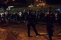 """Nach den pogromartigen Ausschreitungen gegen eine Fluechtlinsunterkunft im saechschen Heidenau am Freitag den 21. August 2015 durch Anwohnerinnen der Ortschaft, kamen am Samstag de 22. August 2015 ca. 250 Menschen in die Ortschaft um ihre Solidaritaet mit den Gefluechteten zu zeigen.<br /> Am Vorabend hatten Rassisten, Nazis und Hooligans sich zum Teil Strassenschlachten mit der Polizei geliefert um zu verhindern, dass Fluechtlinge in einen umgebauten Baumarkt einziehen. Ueber 30 Polizisten wurden dabei verletzt.<br /> Bis in die Abendstunden des 22. August blieb es trotz spuerbarer Anspannung um die Unterkunft ruhig. Im Laufe des Tages wurden immer wieder Gefluechtete mit Reisebussen gebracht was von den wartenenden Heidenauern mit Buh-Rufen begleitet wurde. Vereinzelt wurde auch """"Sieg Heil"""" gerufen, was die Polizei jedoch nicht verfolgte.<br /> Kurz vor 23 Uhr griffen Nazis und Hooligans wie am Vorabend die Polizei mit Steinen, Flaschen, Feuerwerkskoerpern und Baustellenmaterial an. Die Polizei mussten mehrfach den Rueckzug antreten, scheuchte den Mob dann von der Fluechtlingsunterkunft weg. Dabei wurden auch wieder Traenengasgranaten verschossen. Mindestens ein Nazi wurde festgenommen.<br /> Im Bild: Polizeibeamte beobachten die antirassistische Kundgebung.<br /> 22.8.2015, Heidenau/Sachsen<br /> Copyright: Christian-Ditsch.de<br /> [Inhaltsveraendernde Manipulation des Fotos nur nach ausdruecklicher Genehmigung des Fotografen. Vereinbarungen ueber Abtretung von Persoenlichkeitsrechten/Model Release der abgebildeten Person/Personen liegen nicht vor. NO MODEL RELEASE! Nur fuer Redaktionelle Zwecke. Don't publish without copyright Christian-Ditsch.de, Veroeffentlichung nur mit Fotografennennung, sowie gegen Honorar, MwSt. und Beleg. Konto: I N G - D i B a, IBAN DE58500105175400192269, BIC INGDDEFFXXX, Kontakt: post@christian-ditsch.de<br /> Bei der Bearbeitung der Dateiinformationen darf die Urheberkennzeichnung in den EXIF- und  IPTC-Daten nicht entfernt werden, d"""