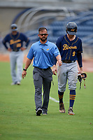 Montgomery Biscuits trainer Kris Russell walks to the dugout with Dalton Kelly (9) after an injury during a Southern League game against the Biloxi Shuckers on May 8, 2019 at MGM Park in Biloxi, Mississippi.  Biloxi defeated Montgomery 4-2.  (Mike Janes/Four Seam Images)