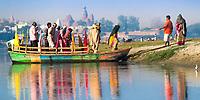Hindus on a colorful boat docking on the bank of sacred Yamuna River, reflecting on the water during Holi celebrations, Mathura Uttar Pradesh, India