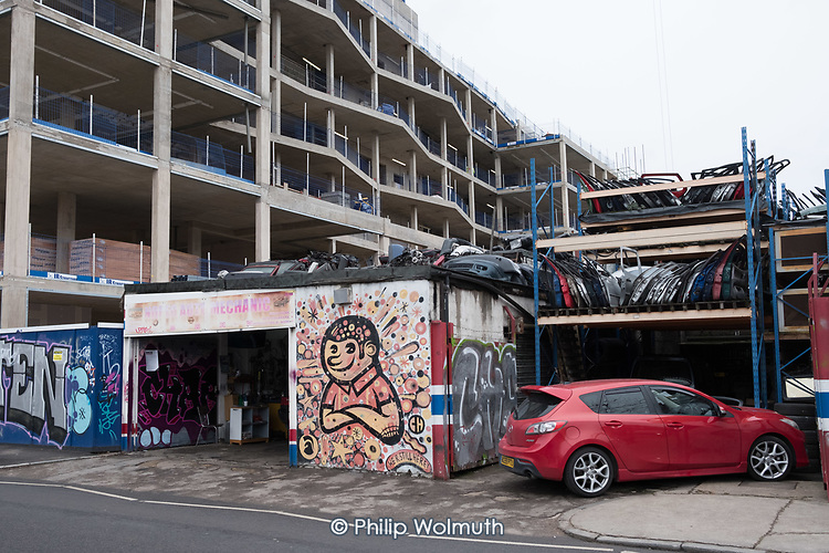 Noreg Auto Mechanic, Rothbury Road, still open, but surrounded by apartment blocks being built for private sale under the Help To Buy scheme in Fish Island, Hackney Wick, an area undergoing rapid gentrification.