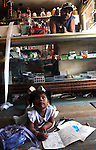 """Journal photo by Ted Richardson:  10/10/2004  Juan Roman watches his daughter Ariel Roman Gonzales, 2, as she takes a break from her coloring books on the floor of Roman's convience store, """"Costa Chica"""", on Sprague St."""