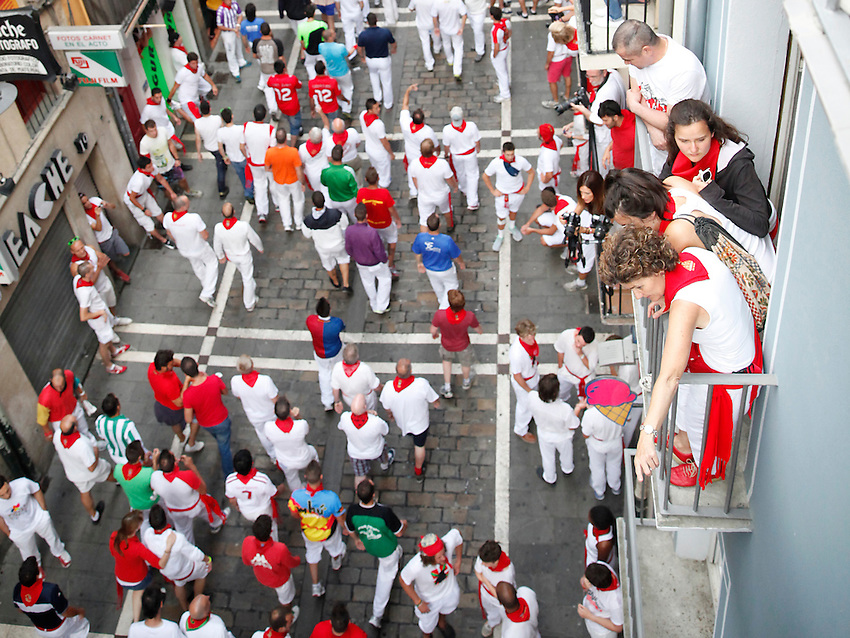 People waits the beginning of the sixth San Fermin Festival´s running of the bulls, on July 12, 2013, in Pamplona, Basque Country. On each day of the eight San Fermin festival days six bulls are released at 8:00 a.m. (0600 GMT) to run from their corral through the narrow, cobbled streets of the old navarre town over an 850-meter (yard) course. Ahead of them are the runners, who try to stay close to the bulls without falling over or being gored. (Ander Gillenea / Bostok Photo)