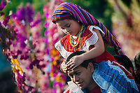 """A Salvadoran man carries his daughter on his shoulders during the procession of the Flower & Palm Festival in Panchimalco, El Salvador, 8 May 2011. On the first Sunday of May, the small town of Panchimalco, lying close to San Salvador, celebrates its two patron saints with a spectacular festivity, known as """"Fiesta de las Flores y Palmas"""". The origin of this event comes from pre-Columbian Maya culture and used to commemorate the start of the rainy season. Women strip the palm branches and skewer flower blooms on them to create large colorful decoration. In the afternoon procession, lead by a male dance group performing a religious dance-drama inspired by the Spanish Reconquest, large altars adorned with flowers are slowly carried by women, dressed in typical costumes, through the steep streets of the town."""