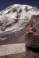 AJ3709, Mount Rainier, Mt. Rainier National Park, Cascades, Cascade Range, Washington, A woman hiker sits on a boulder looking through binoculars at the scenic view of the snow covered Mt. Rainier from Wonderland Trail in the Cascade Mountain Range in Mount Rainier Nat'l Park in the state of Washington.
