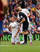 Pictured: Match referee C Pawson (C) sees to injured Jack Cork of Swansea<br /> Re: Premier League match between Crystal Palace and Swansea City at Selhurst Park on Sunday 24 May 2015 in London, England, UK