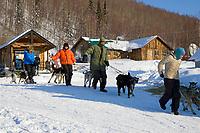 Volunteer dog handlers bring A.Burmeisters sled dog team down from dog park @ Takotna Chkpt 06 Iditarod