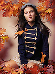 Teenage girl sitting on fallen autumn leaves artistic fall fashion portrait Image © MaximImages, License at https://www.maximimages.com