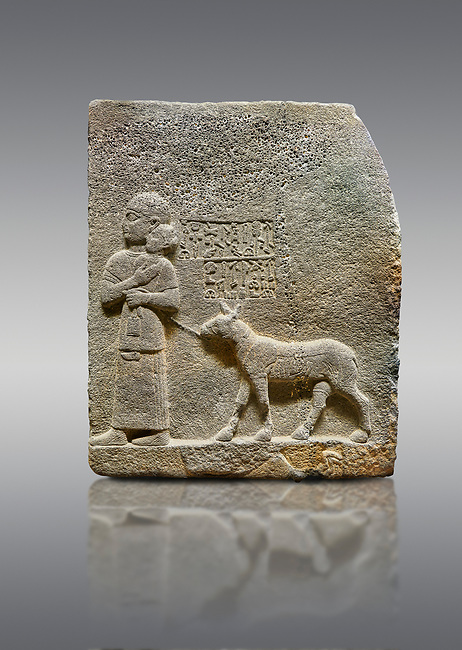 """Picture & image of Hittite monumental relief sculpted orthostat stone panel of Royal Buttress. Basalt, Karkamıs, (Kargamıs), Carchemish (Karkemish), 900-700 B.C. Anatolian Civilisations Museum, Ankara, Turkey<br /> <br /> The queen carries her youngest son. The hieroglyphs located above read; """"and this is Tuwarsais; the prince desired by the ruler, whose exclusiveness has been exposed"""". While the queen carries her son in her lap, she holds the rope of the colt coming behind with her other hand. The muscles of the colt are schematic. <br /> <br /> Against a gray background."""