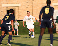 Jeb Brovsky #5 of the University of Notre Dame moves between Julian Robles #3 and Kofi Opare #6 of the University of Michigan during a men's NCAA match at the new Alumni Stadium on September 1 2009 in South Bend, Indiana. Notre Dame won 5-0.