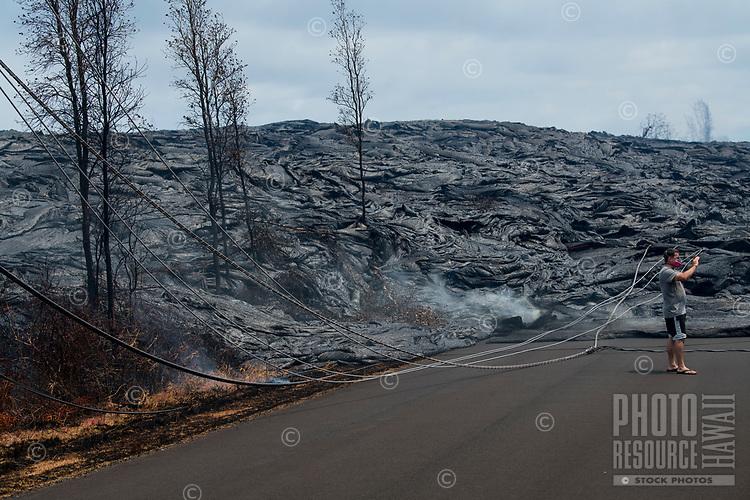 May 2018: A man wearing a face mask takes a photograph of the Kilauea Volcano eruption in Leilani Estates, Puna, Big Island of Hawai'i.