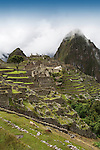 The ancient ruins of Machu Picchu in the mountain mist, at the end of the Inca Trail in Peru.