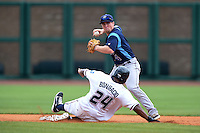 Corpus Christi Hooks second baseman Nolan Fontana (4) throws to first as Jorge Bonifacio (24) slides in during a game against the NW Arkansas Naturals on May 26, 2014 at Arvest Ballpark in Springdale, Arkansas.  NW Arkansas defeated Corpus Christi 5-3.  (Mike Janes/Four Seam Images)