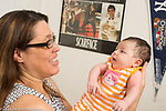 3 week old newborn baby girl held by mother, talked to