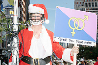 """A man wearing a Santa Claus suit and a helmet with face protection carries a Straight Pride sign that reads """"Thank you Mayor Walsh"""" in the Straight Pride Parade in Boston, Massachusetts, on Sat., August 31, 2019. The parade was organized in reaction to LGBTQ Pride month activities by an organization called Super Happy Fun America."""