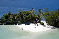 COUPLES HAVING THEIR VACATION ON THE FAMOUS THREE COCONUT ISLAND IN THE ROCK ISLANDS OF PALAU, MICRONESIA
