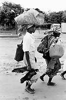 """Mozambique. Province of Gaza. Chokwe. The Limpopo river has flooded in february the whole town."""" Local authorities, fearing a new flood, order the population to leave the town. Families flee with their belongings. The woman carries  a duck in her hand and a bag on her head. © 2000 Didier Ruef"""