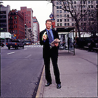Man in suit standing on sidewalk holding a newspaper and a banana<br />
