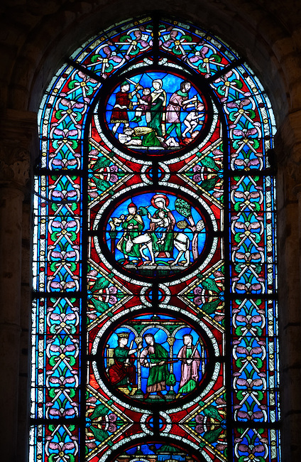 14th century medieval Gothic stained glass window showing scenes from the life of Jesus Christ, (from Bottom up) King Herod ordering the killing of the babies in his kingdom, Mary fleeing with the baby Jesus to Egypt and the Slaying of the Innocents.. The Gothic Cathedral Basilica of Saint Denis ( Basilique Saint-Denis ) Paris, France. A UNESCO World Heritage Site.