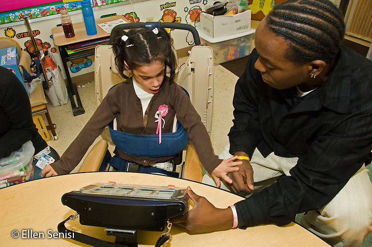MR / Albany, NY.Langan School at Center for Disability Services .Ungraded private school which serves individuals with multiple disabilities.Teaching assistant (African-American) and student interact as teaching assisant helps a student use an alternative and augmentative communication device during speech and language development lesson. Girl: 7, cerebral palsy, nonverbal with expressive and receptive language delays..MR: Wes2, Del16.© Ellen B. Senisi