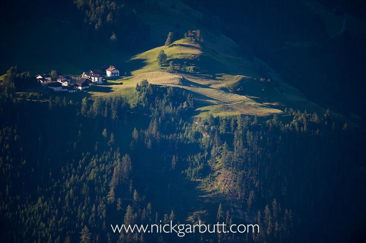 Village, mountain meadow and coniferous forest. Nordtirol, Austrian Alps, Austria, July.