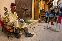 Fes, Morocco.  Tailor Sewing a Garment, Wearing a Fez and a Djellaba.