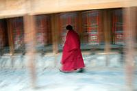 A Tibetan monk turns prayer wheels at Labrang (Chinese Name - Xiahe) Monastery on the Qinghai-Tibetan Plateau. China.