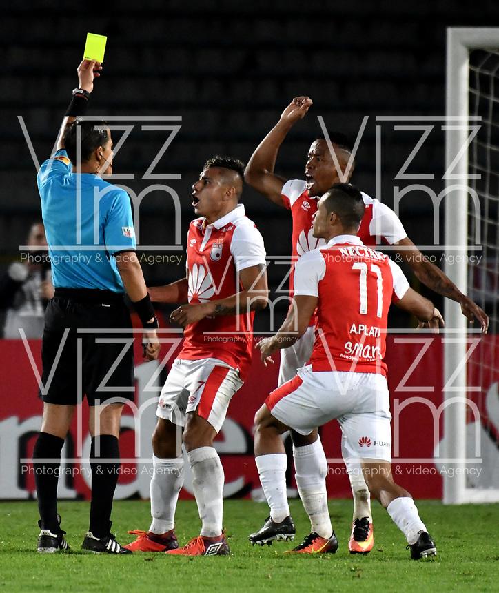 BOGOTA - COLOMBIA - 20 - 02 - 2018: Victor Carrillo (Izq.), arbitro peruano, muestra tarjeta amarilla a Jhon Pajoy (Fuera de Cuadro) durante partido de vuelta entre Independiente Santa Fe (COL) y Santiago Wanderers (CHL), de la fase 3 llave 1, por la Copa Conmebol Libertadores 2018, jugado en el estadio Nemesio Camcho El Campin de la ciudad de Bogota. / Victor Carrillo (L), peruvian referee, shows yellow card to Jhon Pajoy (Out of Frame), during a match for the second leg between Independiente Santa Fe (COL) and Santiago Wanderers (CHL), of the 3rd phase key 1, for the Copa Conmebol Libertadores 2018 at the Nemesio Camacho El Campin Stadium in Bogota city. Photo: VizzorImage  / Luis Ramirez / Staff.