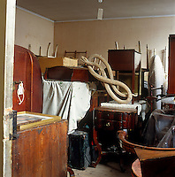 An old dining table, upside-down chairs and a decorative snake are stored in the attic for a rainy day