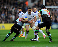 Sam Burgess of Bath Rugby is tackled by George Robson of Harlequins as Mark Lambert of Harlequins lies in wait