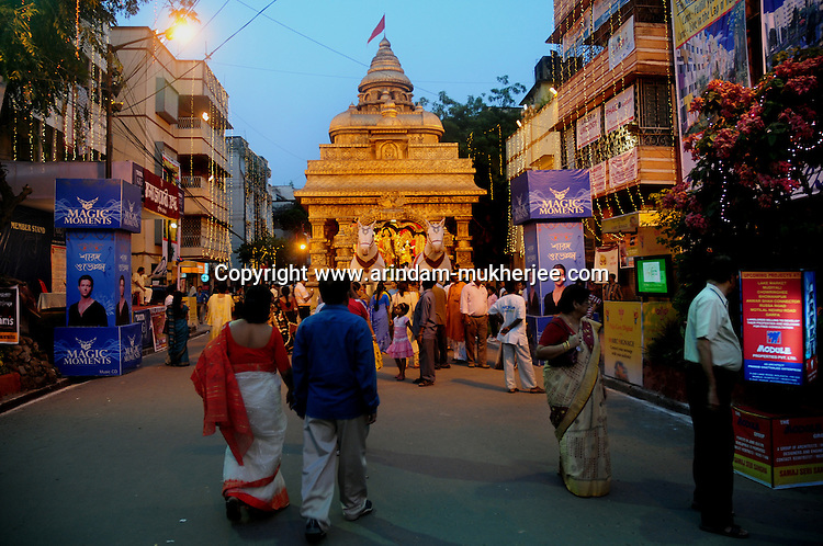 INDIA (West Bengal - Calcutta)  2008, Indian people visiting a Durga Pandal erected on a middle of a street. Durga Puja Festival is the biggest festival among bengalies.  As Calcutta is the capital of West Bengal and cultural hub of  the bengali community Durga puja is held with the maximum pomp and vigour. Ritualistic worship, food, drink, new clothes, visiting friends and relatives places and merryment is a part of it. In this festival the hindus worship a ten handed godess riding on a lion armed wth all possible deadly ancient weapons along with her 4 children (Ganesha - God for sucess, Saraswati - Goddess for arts and education, Laxmi - Goddess of wealth and prosperity, Kartikeya - The god of manly hood and beauty). Durga is symbolised as the women power in Indian Mythology.  In Calcutta people from all the religions enjoy these four days of festival in the moth of October. Now the religious festival has become the biggest cultural extravagenza of Calcutta the cultural capital of India. Artistry and craftsmanship can be seen in different sizes and shapes in form of the idol, the interior decor and as well as the pandals erected on the streets, roads and  parks.- Arindam Mukherjee