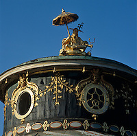 A gilded statue of a seated Chinaman shaded by a parasol on top of the lantern roof of the Chinese Tea Pavilion at Sanssouci Park in Potsdam