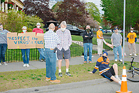 """Holding a sign reading """"Respect the Virus / it kills,"""" people watch as people gather for an anti-lockdown protest organized by the alt-right group Super Happy Fun America near the home of Massachusetts governor Charlie Baker in Swampscott, Massachusetts, on Sat., May 16, 2020. The protest was in defiance of Massachusetts orders mandating face coverings and social distancing and prohibiting gatherings larger than 10 people during the ongoing Coronavirus (COVID-19) global pandemic. The state's stay-at-home order is expected to be updated on May 18, 2020, with a phased reopening plan issued by the governor as COVID-19 cases continue to decrease. Anti-lockdown protests such as this have become a conservative cause and have been celebrated by US president Donald Trump. Many of the protestors displayed pro-Trump messages or wore Trump campaign hats and shirts with phrases including """"Trump 2020"""" and """"Keep America Great."""" Super Happy Fun America, organizers of the protest, are an alt-right organization best known for creating the 2019 Boston Straight Pride Parade."""