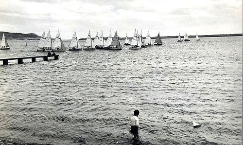 Heron Class start at Kilbarrack – good luck to whoever made that cheeky port tack approach. Meanwhile, in the foreground, a young skipper called Mossy Shanahan with his model yacht has a long way to go in learning about optimum heeling angles for serious windward work. Photo: W G Stokes