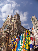 Colorful flags and the Duomo, Siena, Ital
