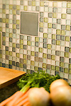 Skewed focus detail shot of a kitchen counter with a beautiful recycled glass tile mosaic as a backsplash, and vegetables in the soft foreground.  Building products made from recycled, salvaged, and/or environmentally friendly materials can be good looking, as well as good for the environment.