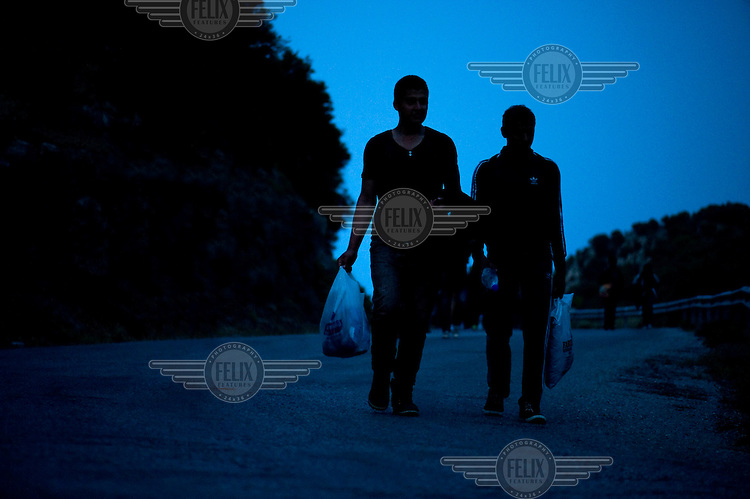 A group of around 50 Afghans - men, women and children - walk the nine hour distance from Skala Sykaminias to the village of Moria on the island of Lesbos where the First Reception Centre for refugees is located. Every day hundreds of refugees, mainly from Syria and Afghanistan, are crossing in small overcrowded inflatable boats the 6 mile channel from the Turkish coast to the island of Lesbos in Greece.