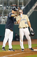 Wake Forest Demon Deacons head coach Tom Walter #32 goes over the situation with base runner Jack Carey #20 during the game against the Miami Hurricanes at NewBridge Bank Park on May 25, 2012 in Winston-Salem, North Carolina.  The Hurricanes defeated the Demon Deacons 6-3.  (Brian Westerholt/Four Seam Images)