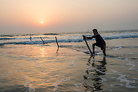 Bangladesh, Cox's Bazar. Fishermen spreading nets in the ocean at sunset. The longest unbroken sea beach in the world running 75 miles.