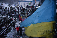An  Ukrainian flag  is waived on top of a barricade under the snow during the protest against new draconian law to ban protests across the country.  Kiev. Ukraine