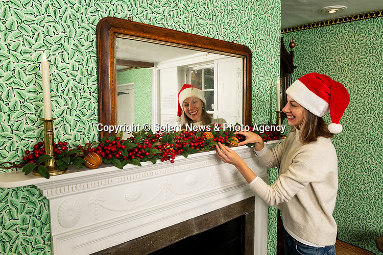 Pictured: Collections manager Sophie Reynolds lays down a Christmas garland on the mantlepiece in the dining parlour as part of the Christmas experience as the Jane Austen's House Museum prepares to reopen to the public for the second time this year. <br /> <br /> Dame Emma Thompson has come to the aid of Jane Austen's former home by providing the voice to a new online Christmas experience.<br /> <br /> From today fans of the novelist can hear the actor - who won an Oscar for her screenplay for the 1995 film adaptation Sense and Sensibility - read from some of her books and letters.<br /> <br /> The 61 year old has recorded eight tracks for the Jane Austen House museum, which showcase her 'dry wit and enjoyment' of yuletide traditions.<br /> <br /> This week staff at the House in Chawton, Hants, have been putting up Christmas decorations in the hope that they will be able to reopen on December 3 if restrictions are eased, so visitors can enjoy the experience first hand.   SEE OUR COPY FOR FULL DETAILS.<br /> <br /> © Jordan Pettitt/Solent News & Photo Agency<br /> UK +44 (0) 2380 458800